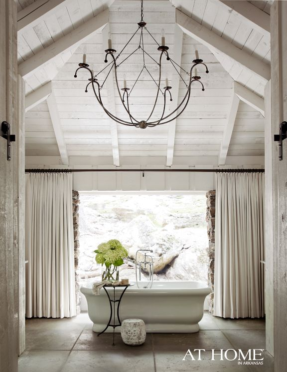 A complete and well thought out space with beautiful architectural details and scale, lovely texture just outside the window and simple but elegant decoration. Everything from the choice  of fabric on the windows to the chandelier and tub, speak to elegance, refinement and sophistication.
